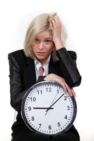 anguished: Stressed blond woman with clock