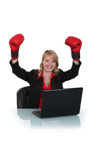 Businesswoman sat wearing boxing gloves photo