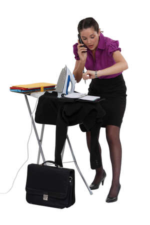 haste: Late businesswoman ironing a suit jacket