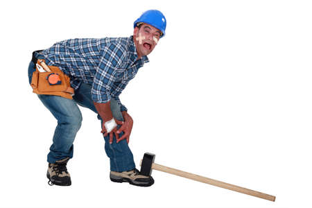whack: Builder dropping hammer on foot Stock Photo