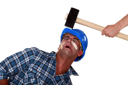 personal injury: Man being hit over the head by hammer Stock Photo