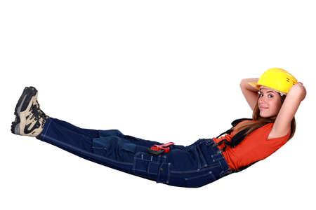 tradeswoman: Tradeswoman lying in an invisible hammock Stock Photo
