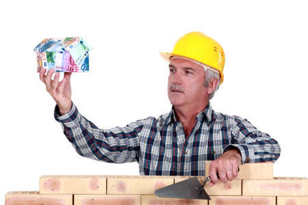 Builder with a house made of money Stock Photo - 18304585
