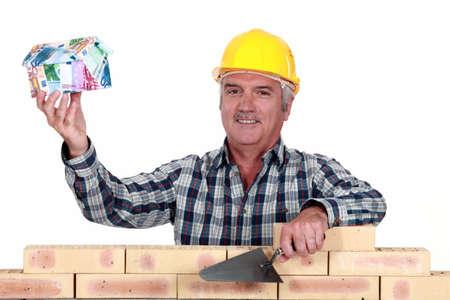 stonemasonry: Tradesman holding up a house model make out of money Stock Photo