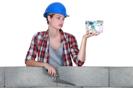 acquittal: female mason holding a bunch of bills and looking very disappointed