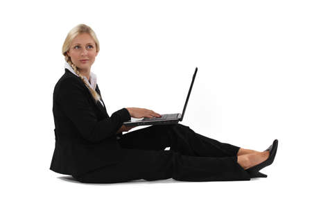 A businesswoman sitting on the floor with her laptop. photo