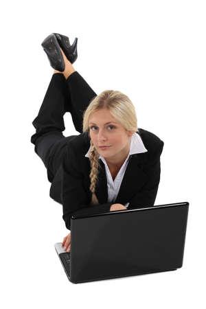 impassive: Businesswoman lying on the floor with her laptop Stock Photo