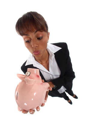 Businesswoman looking at a piggy bank photo