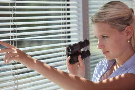 A spy peering through some blinds Stock Photo