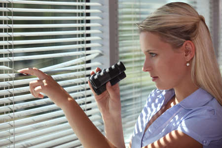 investigating: Nosy woman peering through some blinds Stock Photo