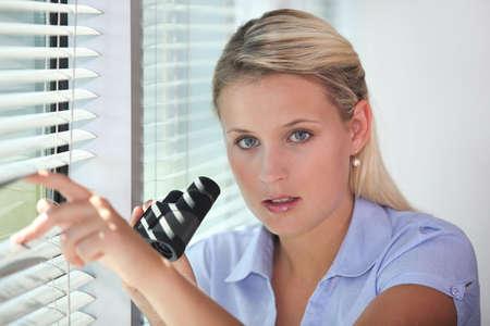 nosey: Woman peering through blinds with binoculars