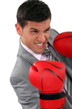 young businessman wearing boxing gloves photo