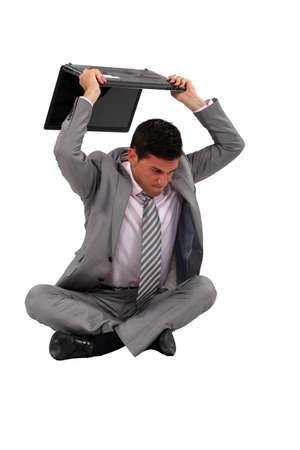 damaging: Mad worker destroying computer