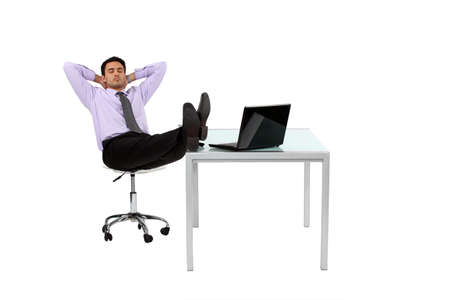 wishful: Businessman resting his feet on desk Stock Photo