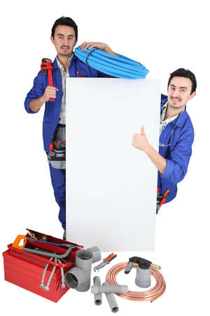 Twin tradesmen standing around a blank sign photo