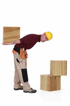 Builder with large blocks of wood photo
