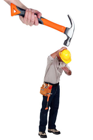 Builder being attacked by giant hammer photo
