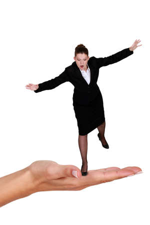 Businesswoman balancing on giant hand photo