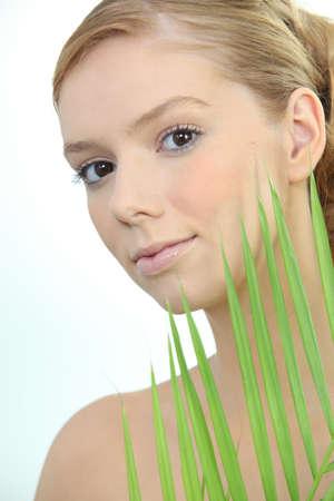 plantlife: Blond woman holding leaf Stock Photo