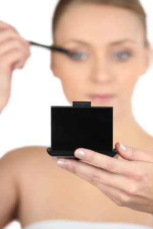 compact: Woman applying mascara looking at a compact mirror