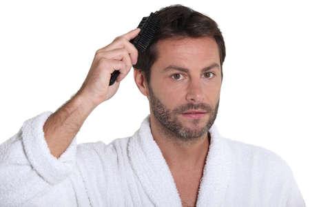 toweling: Man wearing a toweling robe brushing his hair