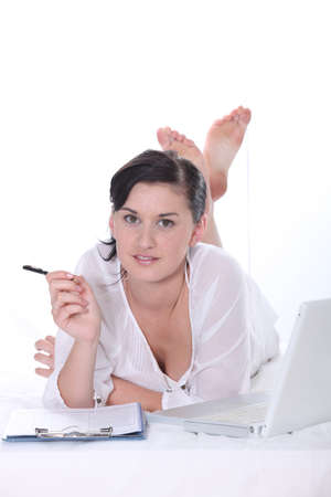 bare feet girl: Young woman lying down with a laptop computer and clipboard