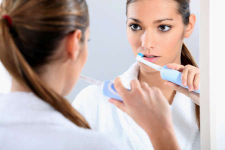 dentalcare: Woman with an electric toothbrush