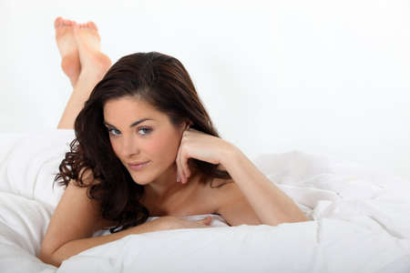 Brunette woman lying in bed photo
