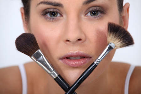 Closeup of a woman with makeup brushes photo