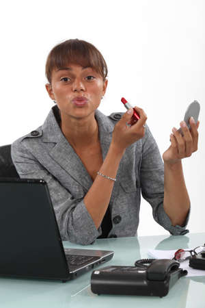 puckering lips: Woman applying lipstick at the office Stock Photo