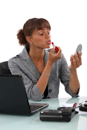 highlighted hair: Woman applying lipstick at the office Stock Photo