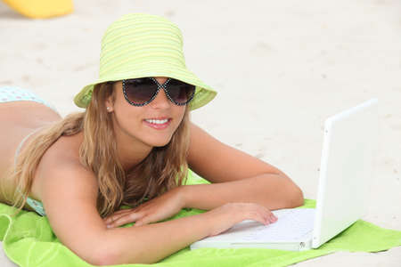 minicomputer: portrait of a young woman on the beach with laptop