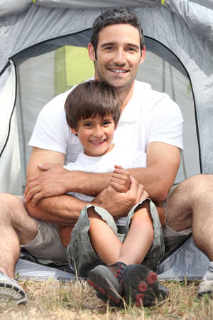 Father and son in front of their tent photo