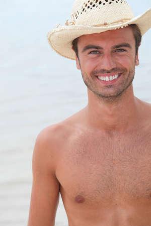 Man stood on the beach wearing straw hat photo