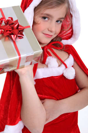 aloft: Girl dressed in a Santa costume holding aloft a present Stock Photo