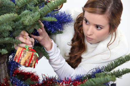 Girl hanging gift from Christmas tree Stock Photo