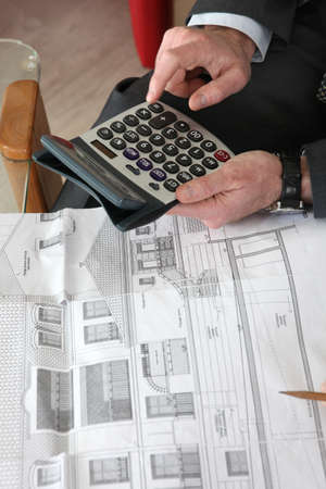 Architect sat with blueprints and calculator photo