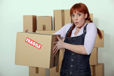 carrying box: Woman carrying fragile box