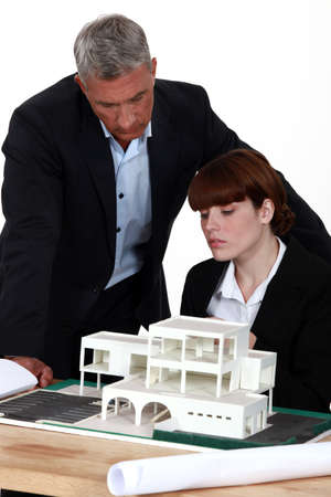 Architect and assistant looking at model house Stock Photo - 18464428
