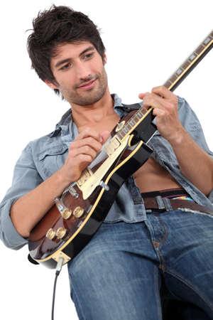 melodious: young man playing guitar