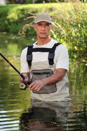 wading: Fisherman wading in river Stock Photo