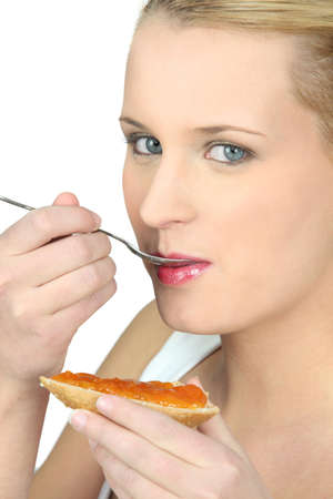 contentedness: Woman eating bread and jam