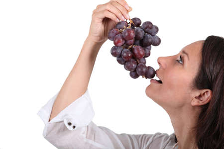 Woman eating a bunch of grapes photo