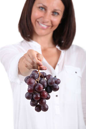 largesse: 35 years old woman giving a red grape