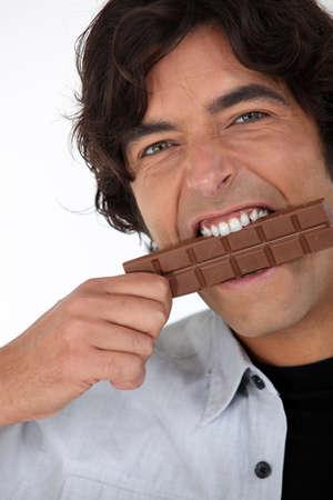 munch: Man eating a bar of chocolate Stock Photo
