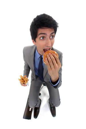 Businessman scoffing a burger and fries photo