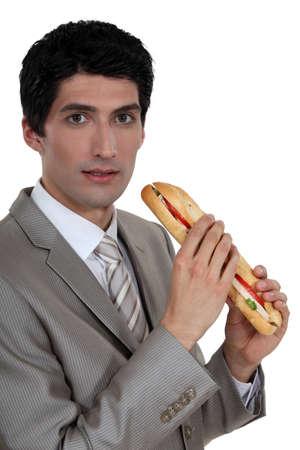 eat out: Businessman eating a sandwich