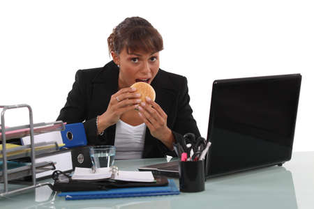 Businesswoman eating fast-food at her desk photo