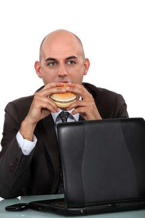 businessman eating a hamburger photo