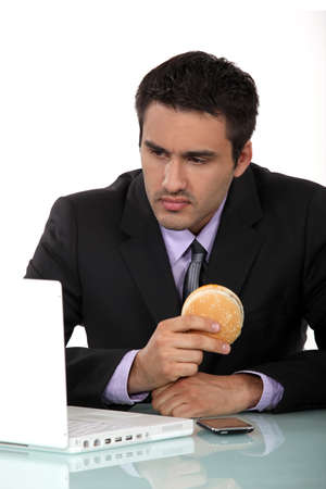 Man sat at his desk eating hamburger photo